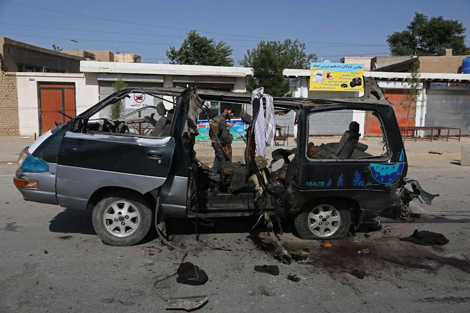 A security personnel stands next to a damaged vehicle at the site of an explosion in Kabul on June 3, 2021. At least seven people have been killed in two new attacks on minivans. (AFP via Getty Images)