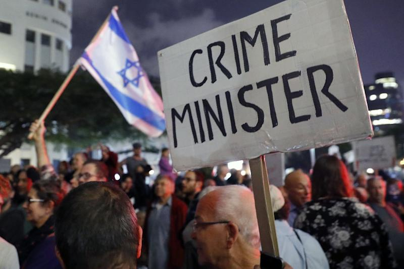 """Israelis take part in a demonstration titled the """"March of Shame"""", as they protest against alleged corruption in Prime Minister Benjamin Netanyahu's government in Tel Aviv on December 23, 2017 (AFP Photo/JACK GUEZ)"""