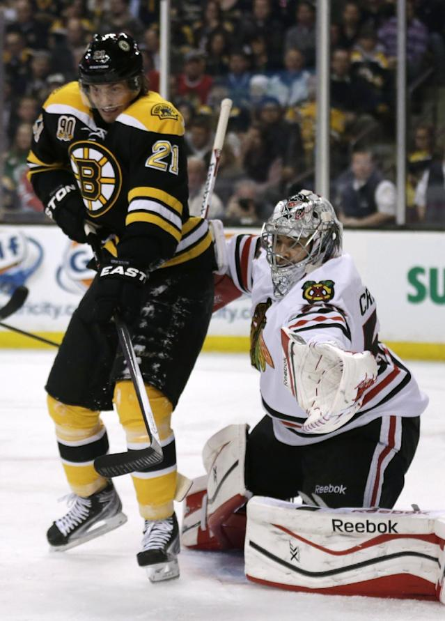 Boston Bruins left wing Loui Eriksson (21) tries to tip the puck on a shot as Chicago Blackhawks goalie Corey Crawford (50) makes a save during the second period of an NHL hockey game, Thursday, March 27, 2014, in Boston. (AP Photo/Charles Krupa)