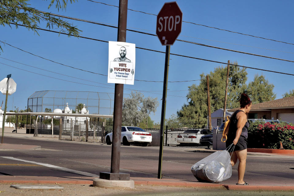 In this June 18, 2020, photo, a woman walks to a bus stop in Guadalupe, Ariz. As the coronavirus spreads deeper across America, it's ravaging through the homes and communities of Latinos from the suburbs of the nation's capital to the farm fields of Florida to the sprawling suburbs of Phoenix and countless communities in between. (AP Photo/Matt York)