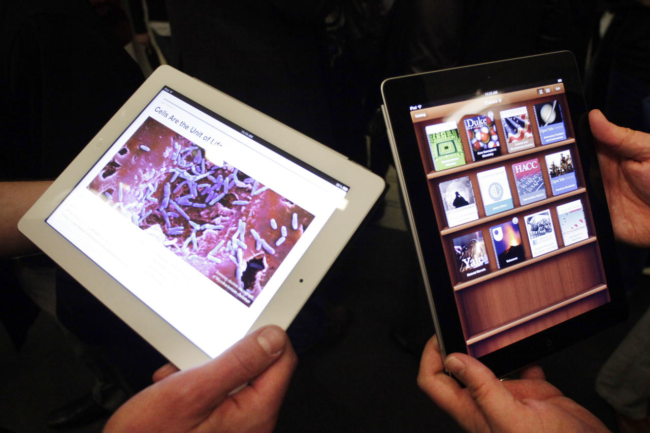 Apple employees demonstrate interactive features of iBooks 2 for iPad, Thursday, Jan. 19, 2012 in New York. IBooks 2 will be able to display books with videos and other interactive features. (AP Photo/Mark Lennihan)