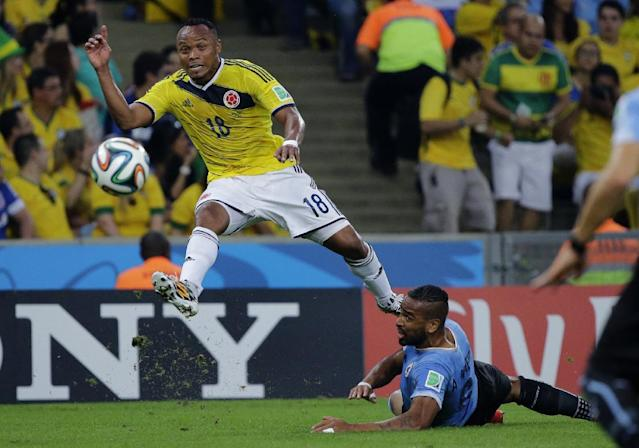 Colombia's Juan Zuniga, left, gets in a shot despite the challenge of Uruguay's Alvaro Pereira during the World Cup round of 16 soccer match between Colombia and Uruguay at the Maracana Stadium in Rio de Janeiro, Brazil, Saturday, June 28, 2014. (AP Photo/Sergei Grits)