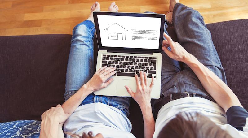Couple win laptop on their lap looking at a house outline