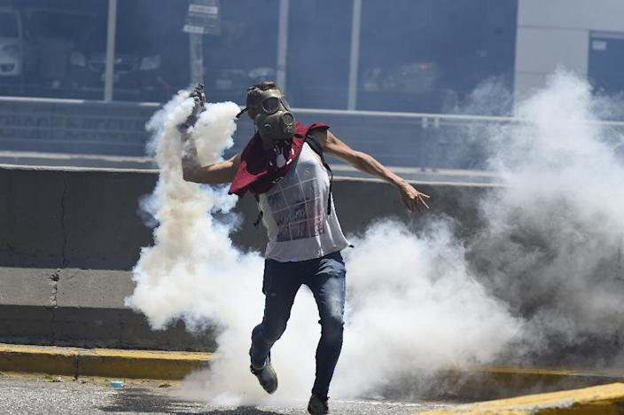A demonstrator against Nicolas Maduro's government returns a tear gas during clashes with riot police at eastern Caracas on April 8, 2017 (AFP Photo/JUAN BARRETO )