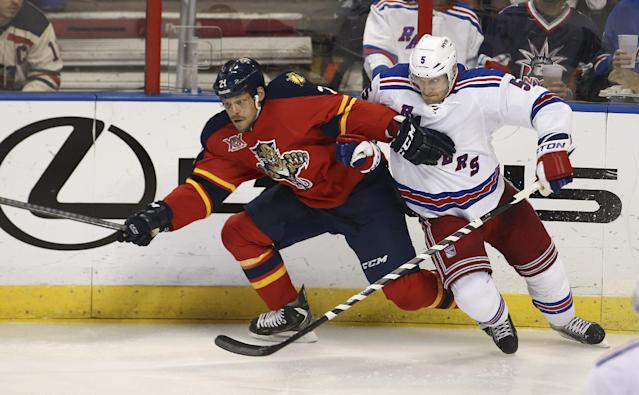 Florida Panthers' Krys Barch (21) and New York Rangers' Dan Girardi (5) battle for the puck during the second period of an NHL hockey game in Sunrise, Fla., Wednesday, Nov. 27, 2013. (AP Photo/J Pat Carter)