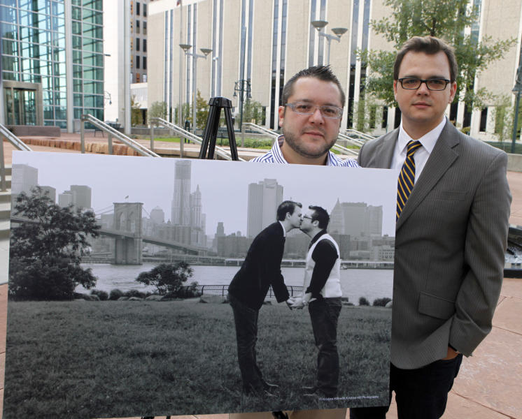 Tom Privitere, left, and his partner Brian Edwards pose at the federal courthouse in Denver on Wednesday, Sept. 26, 2012, with the engagement photo that was altered and used in a political campaign. The New York skyline was replaced with a winter scene. They and the photographer who took the photo have filed a lawsuit over the misuse of the photograph. (AP Photo/Ed Andrieski)