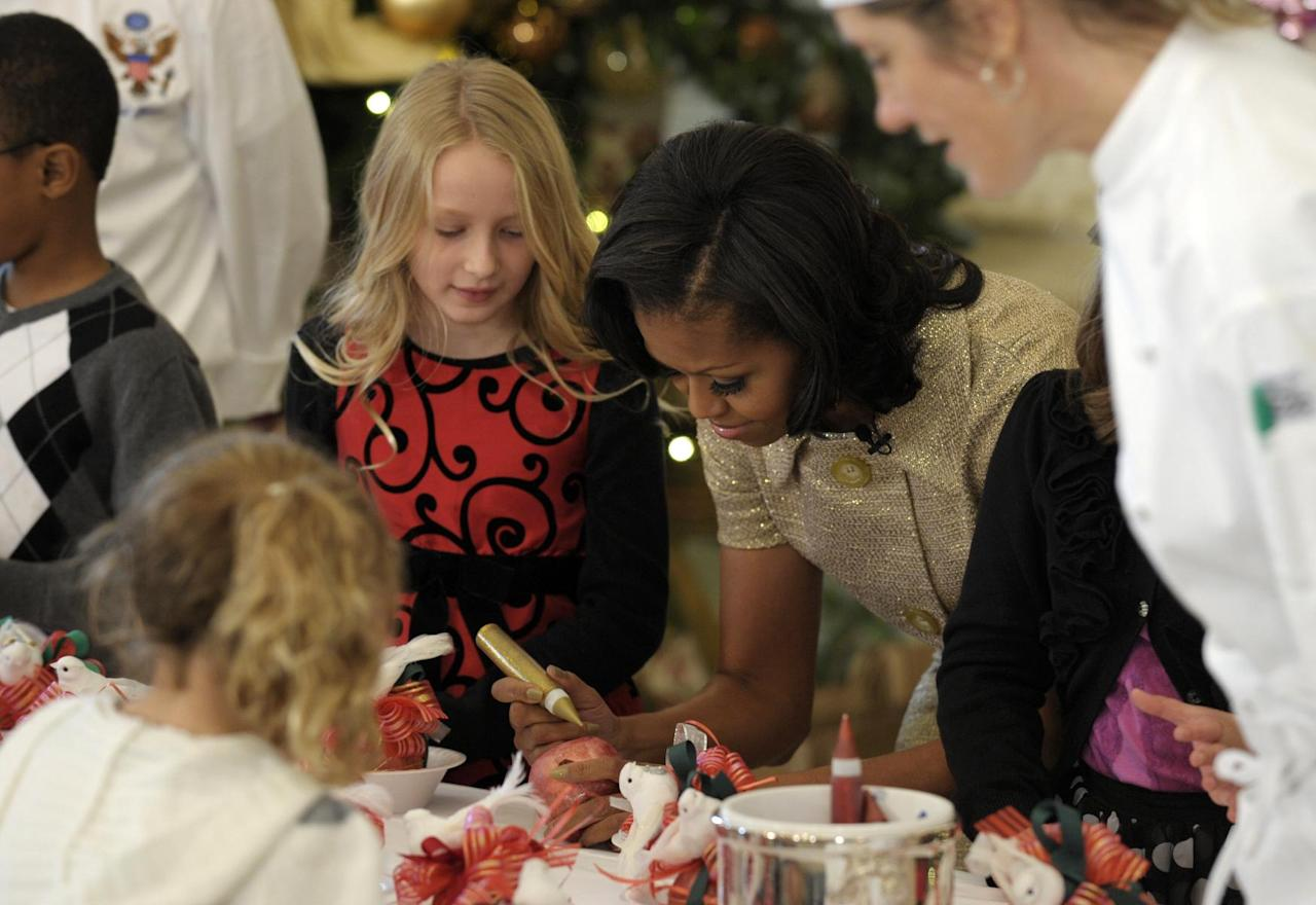First lady Michelle Obama decorates a lollipop during a holiday decoration preview at the White House in Washington, Wednesday, Nov. 28, 2012. Obama joined school children as they decorated holiday treats. (AP Photo/Susan Walsh)