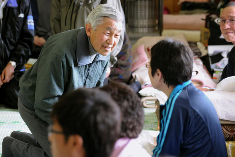 FILE - In this May 6, 2011, file photo, Emperor Akihito kneels down as he speaks with a woman during his visit to a refugee center in Kamaishi, a city severely damaged by the March 11 earthquake and tsunami, in Iwate Prefecture, northeastern Japan. The outpouring of emotion was earned through much smaller moments, such as his visit in 2011, wearing a windbreaker instead of his usual suit, to see victims of a massive earthquake, tsunami and nuclear meltdown. (Kyodo News via AP, File)