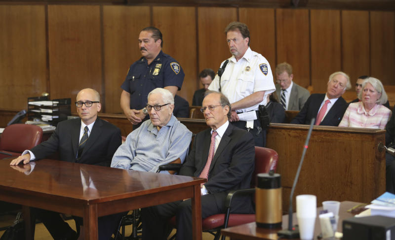 Anthony Marshall, center, sits with his attorneys in criminal court as his wife Charlene Marshall, far right, sits in the gallery, Friday, June 21, 2013 in New York. The 89-year-old heir convicted of helping himself to his mother Brooke Astor's fortune surrendered Friday after years of fighting his conviction to begin his prison term. (AP Photo/Mary Altaffer)
