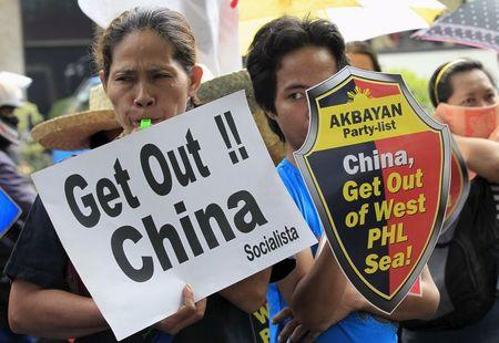 Protesters make noise during a rally regarding the disputed islands in the South China Sea, in front of the Chinese Consulate in Makati city