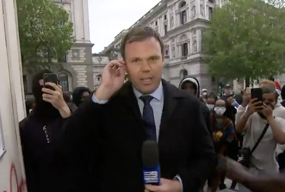 Pictured is Ben Avery reporting for Nine News with a crowd of protesters behind him.