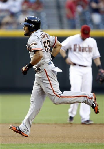 San Francisco Giants' Melky Carbrera, left, trots around the bases in front of Arizona Diamondbacks shortstop Willie Bloomquist, right, after hitting a solo home run off Diamondbacks pitcher Patrick Corbin in the first inning of a baseball game Friday, May 11, 2012, in Phoenix. (AP Photo/Paul Connors)