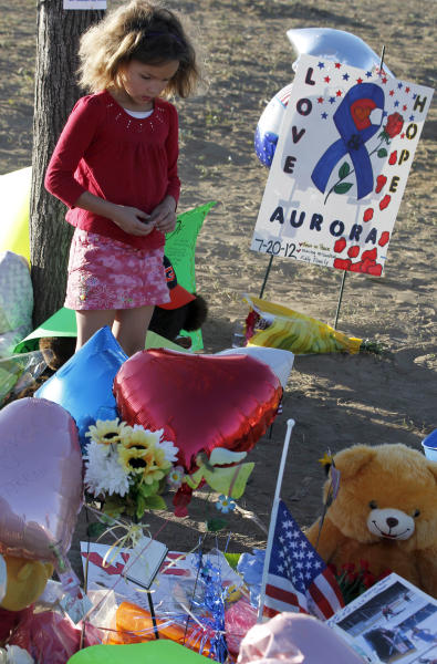 "Serenity Brydon, 7, from Aurora, looks at a memorial near the the Century 16 movie theater Sunday, July 22, 2012, in Aurora, Colo. Twelve people were killed and dozens were injured in a shooting attack early Friday at the packed theater during a showing of the Batman movie, ""The Dark Knight Rises."" Police have identified the suspected shooter as James Holmes, 24. (AP Photo/Alex Brandon)"