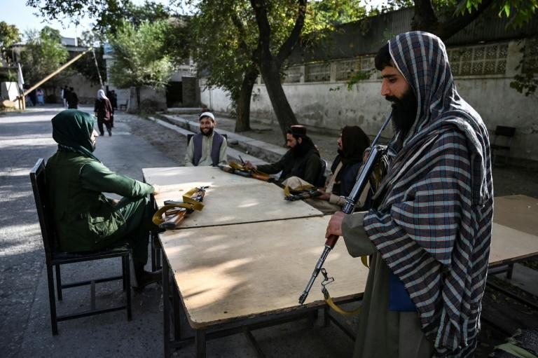 Taliban fighters sit outside the passport office after its reopening for applications in Kabul (AFP/WAKIL KOHSAR)