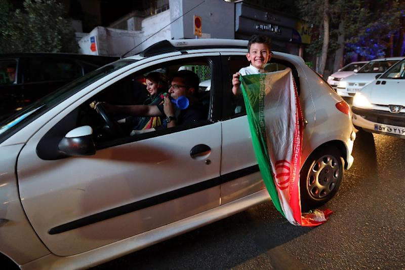 An Iranian boy waves the national flag during celebrations in northern Tehran on July 14, 2015, after the country's nuclear negotiating team struck a deal with world powers (AFP Photo/Atta Kenare)