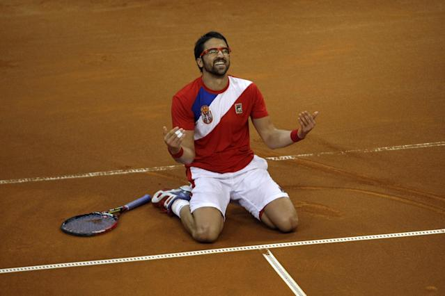 Serbia's Janko Tipsarevic falls to his knees as he celebrates his team's victory at the Davis Cup semifinal against Canada in Belgrade, Serbia, Sunday, Sept. 15, 2013. (AP Photo/Marko Drobnjakovic)