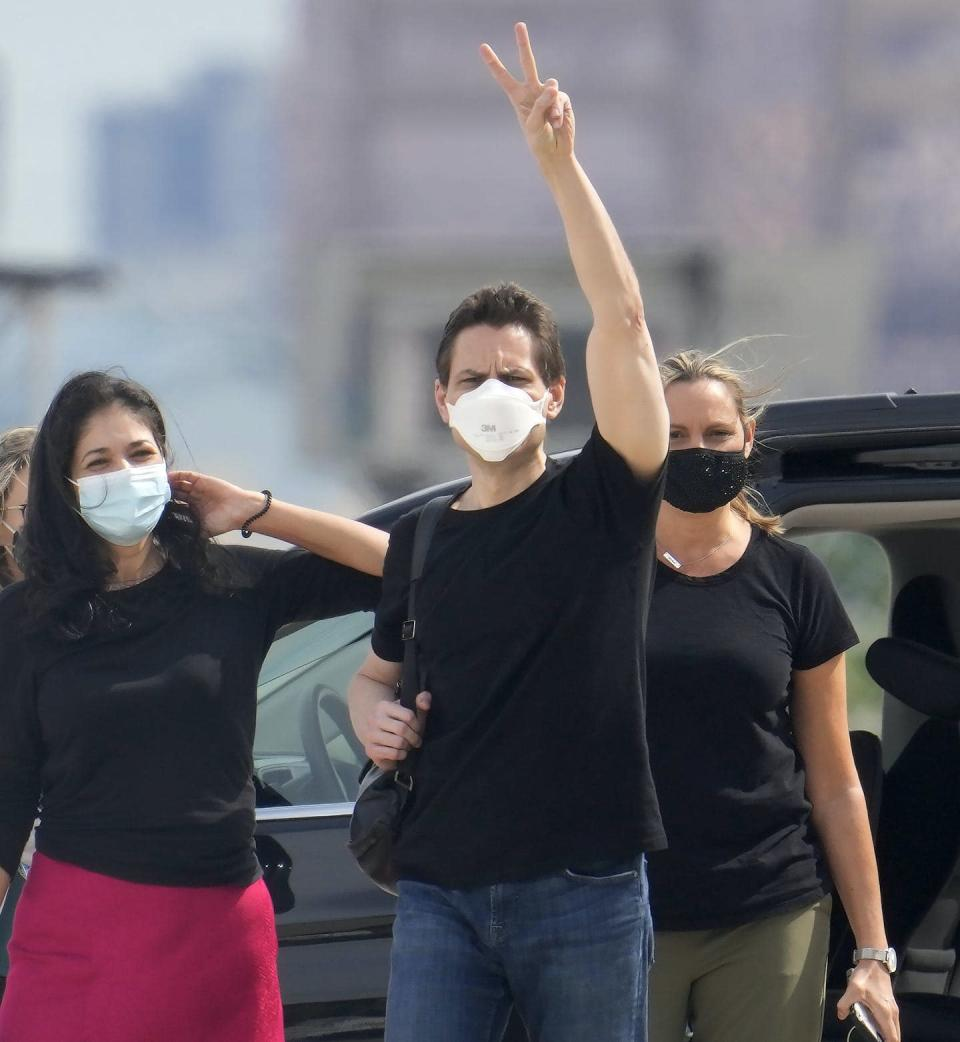 """<span class=""""caption"""">Michael Kovrig flashes a V for victory sign alongside his wife and sister at Pearson International Airport after his return to Canada. </span> <span class=""""attribution""""><span class=""""source"""">THE CANADIAN PRESS/Frank Gunn </span></span>"""