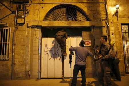 Israeli security forces search the area where, according to Israeli police spokesperson, at least 10 Israelis were stabbed, in the popular Jaffa port area of Tel Aviv, Israel