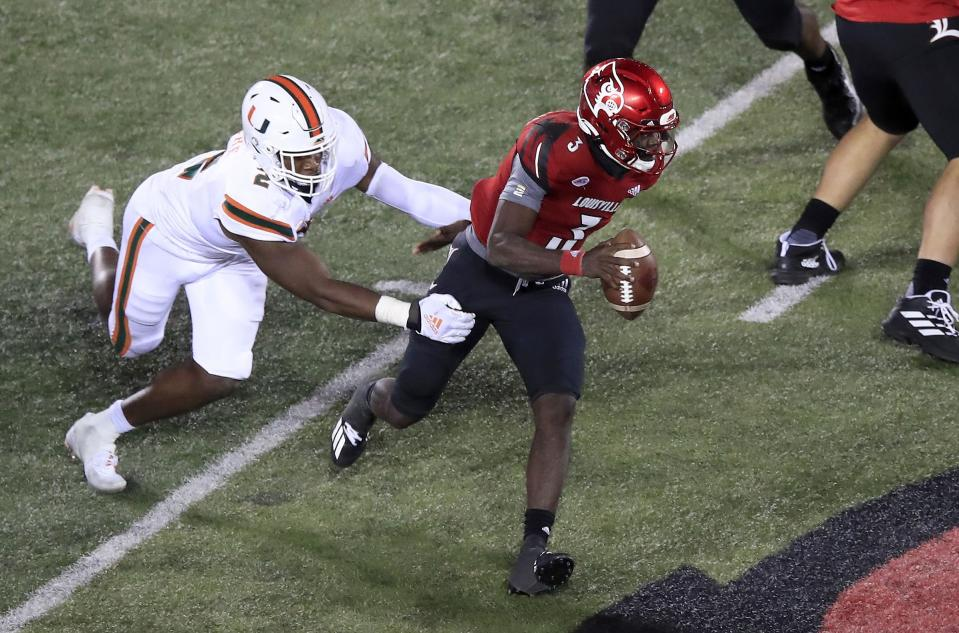 Louisville's Malik Cunningham runs with the ball while defended by Quincy Roche #2 of the Miami Hurricanes at Cardinal Stadium on September 19, 2020 in Louisville, Kentucky. (Andy Lyons/Getty Images)