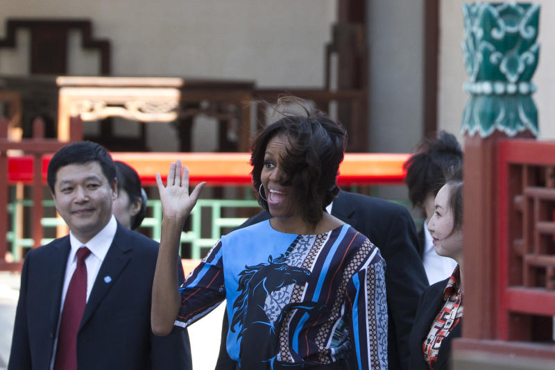 U.S. first lady Michelle Obama waves to a group of American schoolchildren who are visiting China during their spring break before they watch a Peking opera performance at the Summer Palace in Beijing, Saturday, March 22, 2014. (AP Photo/Alexander F. Yuan)