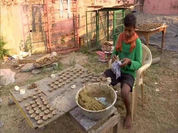 A worker in the Gaushala making lamps out of cow dung and fuller's earth. (Photo/ANI)