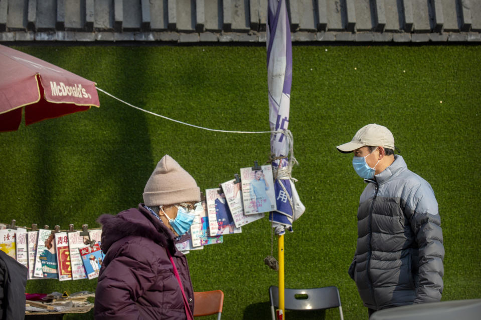 People wearing face masks to protect against the spread of the coronavirus walk past a newsstand in Beijing, Wednesday, Jan. 20, 2021. China is now dealing with coronavirus outbreaks across its frigid northeast, prompting additional lockdowns and travel bans. (AP Photo/Mark Schiefelbein)