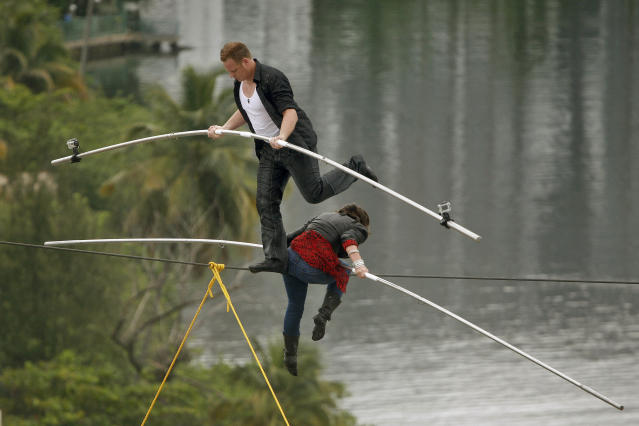 """FILE- In this June 4, 2011 file photo, high-wire acrobats Delilah Wallenda, right, lowers her head as her son Nik Wallenda, left, crosses over her during their high-wire act where the two simultaneously walked across a 300-foot-long wire suspended 100 feet in the air between two towers of the Conrad Condado Plaza Hotel in San Juan, Puerto Rico. They were honoring Nik's great-grandfather, Karl Wallenda, who tried to perform the same feat in 1978 but fell to his death at age 73. On Friday, June 15, 2012, Karl's great grandson, Nick Wallenda, will attempt a high wire walk over Niagara Falls on live television, hoping to write his famous family's name into the 153-year-old legend of daredevils who've """"conquered"""" the natural wonder. (AP Photo/Ricardo Arduengo, File)"""