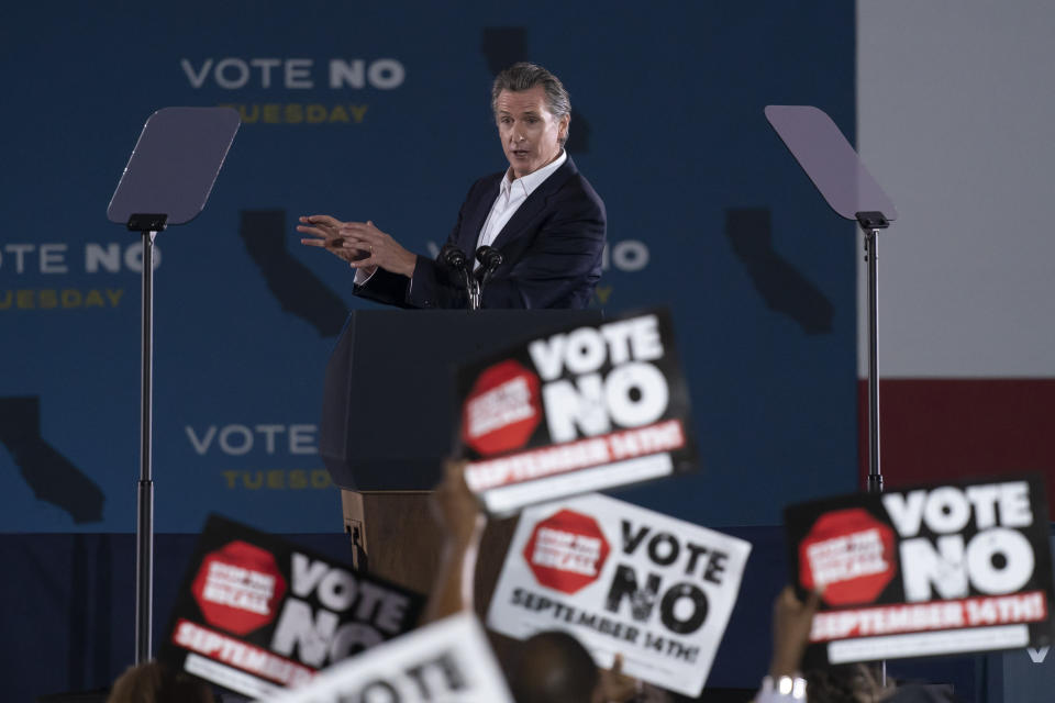 Supporters hold up signs as California Gov. Gavin Newsom speaks at a rally ahead of the California gubernatorial recall election Monday, Sept. 13, 2021, in Long Beach, Calif. (AP Photo/Jae C. Hong)