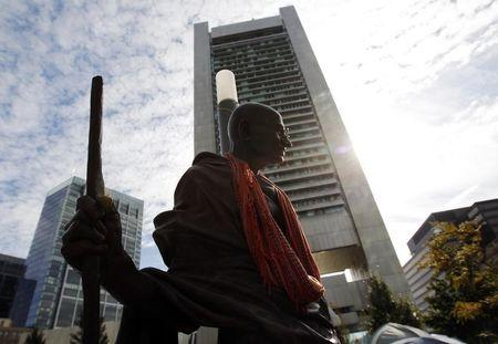 A statue of Mahatma Gandhi stands in the Occupy Boston encampment, with Boston's Federal Reserve Building in the background, in Boston