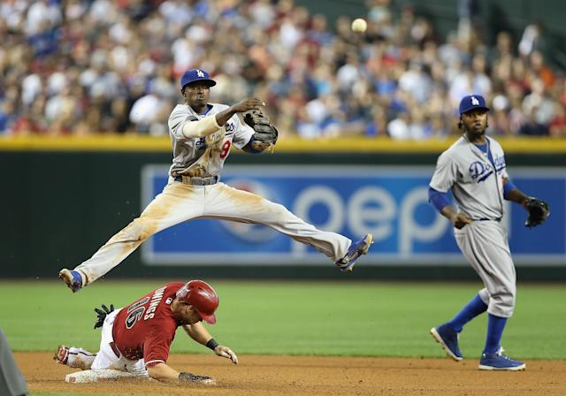 PHOENIX, AZ - APRIL 13: Infielder Dee Gordon #9 of the Los Angeles Dodgers makes a leaping throw over the sliding Chris Owings #16 of the Arizona Diamondbacks to complete a double play during the fouth inning of the MLB game at Chase Field on April 13, 2014 in Phoenix, Arizona. (Photo by Christian Petersen/Getty Images)
