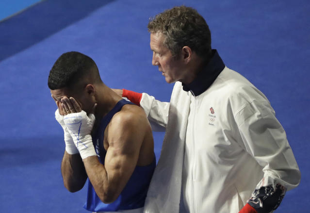 <p>Britain's Galal Yafai is comforted by his coach after losing to Cuba's Joahnys Argilagos in a men's light flyweight 49-kg preliminary boxing match at the Summer Olympics in Rio de Janeiro, Brazil, Monday, Aug. 8, 2016. (AP Photo/Jae C. Hong) </p>