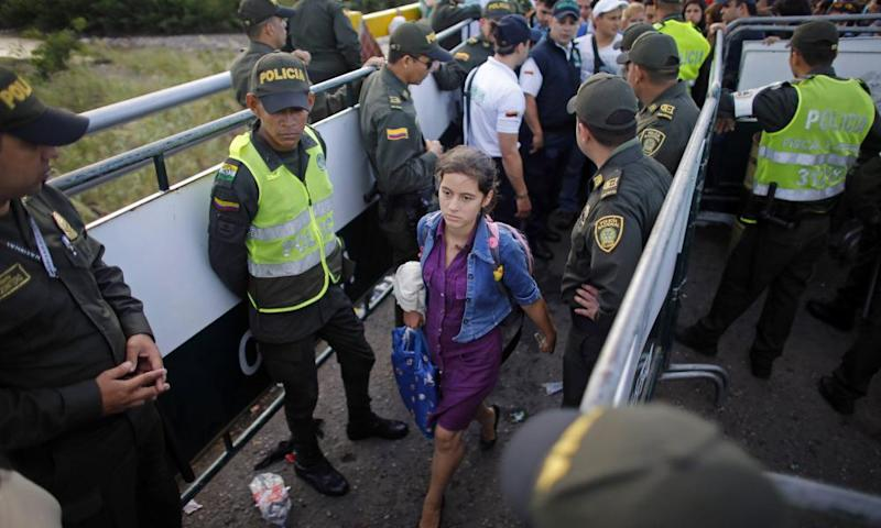 Police stand guard as a Venezuelan woman crosses into Colombia through a bridge linking San Antonio del Tachira, Venezuela, with Cucuta, Colombia.