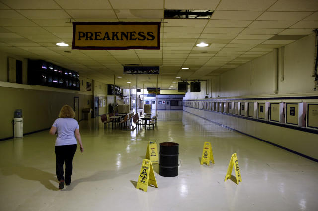 FILE - In this May 15, 2018, file photo, a woman walks past a barrel catching water from a leaking ceiling at Pimlico Race Course as preparations take place for the Preakness Stakes horse race in Baltimore. The future of Pimlico has turned into a tug of war involving city officials, who want it to stay in Baltimore, and the owners of the track, who long to move the second jewel of the Triple Crown to nearby Laurel. (AP Photo/Patrick Semansky, File)