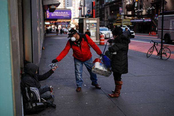 PHOTO: Virna Munoz-Guzman, 52, right, and her husband Felix, wear protective gloves and masks due to COVID-19 concerns as they hand out disposable gloves and sanitizing wipes to people who are homeless on 42nd Street, March 21, 2020, in New York. (John Minchillo/AP)