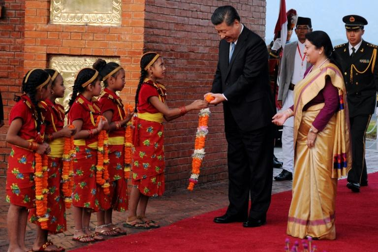 Nepalese girls present garlands to Chinese President Xi Jinping (C) as Nepal's president Bidhya Devi Bhandari (R) looks on during a welcome ceremony at the Tribhuvan International Airport in Kathmandu