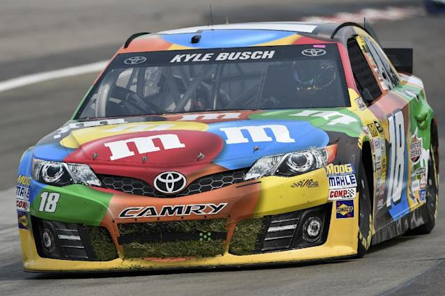 FILE - In this Aug. 8, 2014, file photo, the grille of Kyle Busch's (18) race car is full of grass after he went off course during a practice session for a NASCAR Sprint Cup Series auto race at Watkins Glen International in Watkins Glen N.Y. Mars has signed multi-year sponsorship deals with both Joe Gibbs Racing and NASCAR. The agreement announced Wednesday, Aug. 13, 2014, keeps Mars on the No. 18 Toyota driven by Kyle Busch. (AP Photo/Derik Hamilton, File)