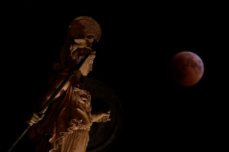 A full moon rises during a lunar eclipse behind the statue of the ancient goddess Athena in Athens