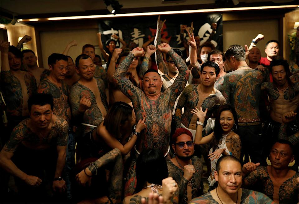 A group of people with body tattoos pose for a photo