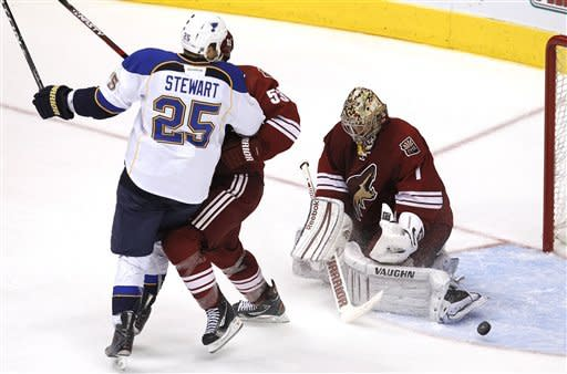 Phoenix Coyotes goalie Jason LaBarbera (1) makes a save as Derek Morris tangles with St. Louis Blues' Chris Stewart (25) in front of the goal during the second period of an NHL hockey game, Sunday, March 25, 2012, in Glendale, Ariz.(AP Photo/Ross D. Franklin)