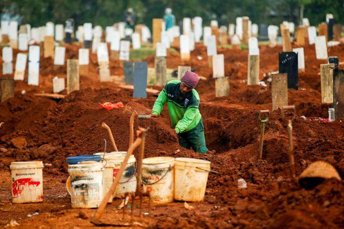 A gravedigger standing in a plot surrounded by gravestones