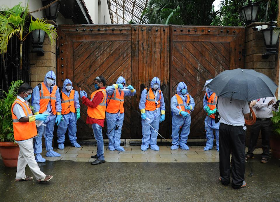 Municipal workers wearing personal protective equipment suits (PPE) stand outside the gate of Bollywood actor Amitabh Bachchan's bungalow. Bollywood actor Amitabh Bachchan tested positive for coronavirus and has been admitted to a hospital where he is being kept in quarantine. The actor requested those who had come in close proximity in the past ten days to get themselves tested for the virus. (Photo by Ashish Vaishnav/SOPA Images/LightRocket via Getty Images)