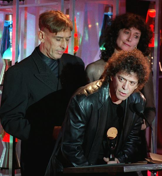FILE - In this Jan. 17, 1996 file photo, Lou Reed takes the podium as the Velvet Underground, the group he once headed, is inducted into the Rock and Roll Hall of Fame during a ceremony in New York s Waldorf-Astoria Hotel. Band mate John Cale is at left, and at right is Martha Morrison, accepting for late band member Sterling Morrison. Punk-poet, rock legend Lou Reed is dead of a liver-related ailment, his literary agen said Sunday, Oct. 27, 2013. He was 71. (AP Photo/Mark Lennihan, File)