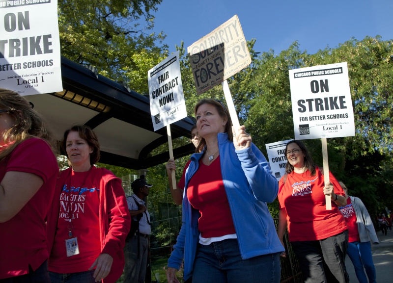 """Public school teachers picket outside Amundsen High School on the first day of a strike by the Chicago Teachers Union, Monday, Sept. 10, 2012, in Chicago. The school is one of more than 140 schools in the Chicago Public Schools' """"Children First"""" contingency plan, which feeds and houses students for four hours during the strike. (AP Photo/Sitthixay Ditthavong)"""