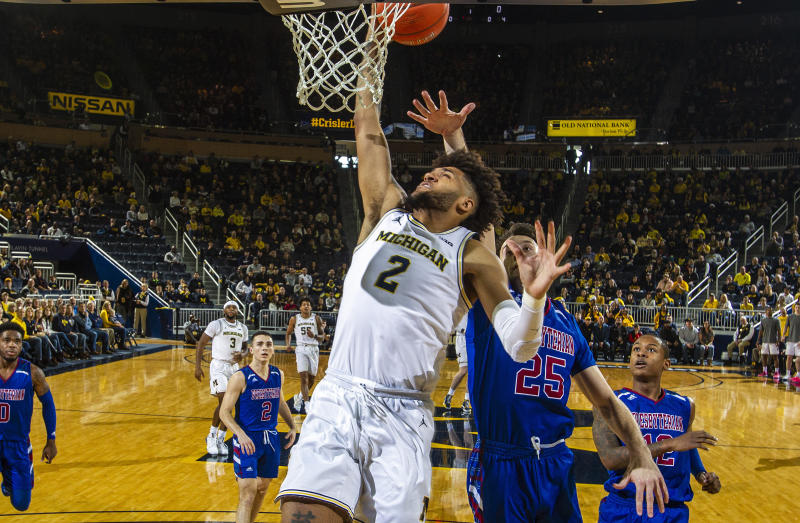Michigan forward Isaiah Livers (2) attempts a dunk ahead of Presbyterian guard JC Younger (25) in the first half of an NCAA college basketball game at Crisler Center in Ann Arbor, Mich., Saturday, Dec. 21, 2019. (AP Photo/Tony Ding)