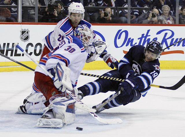New York Rangers goaltender Henrik Lundqvist (30) saves a shot from Winnipeg Jets' Jim Slater (19) as Rangers' Martin St. Louis helps to defend during the second period of an NHL game in Winnipeg, Manitoba, Friday, March 14, 2014. (AP Photo/The Canadian Press, John Woods)
