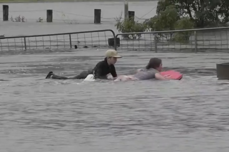 Two children use bodyboards to navigate a flooded property in NSW.
