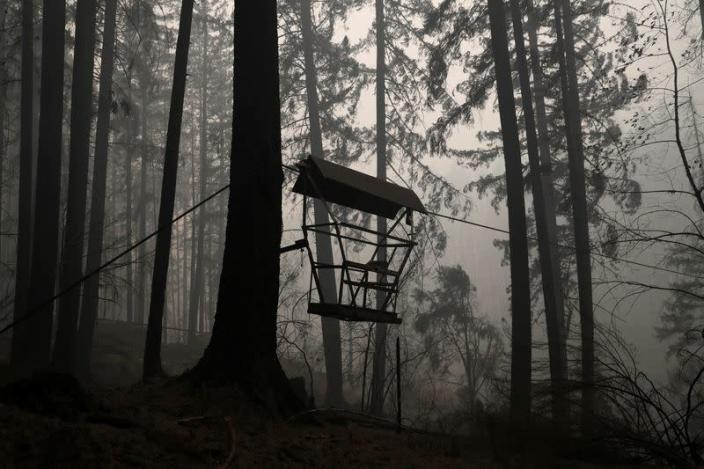 The remains of a fire damaged chairlift hangs as smoke billows in the aftermath of the Beachie Creek fire near Detroit, Oregon