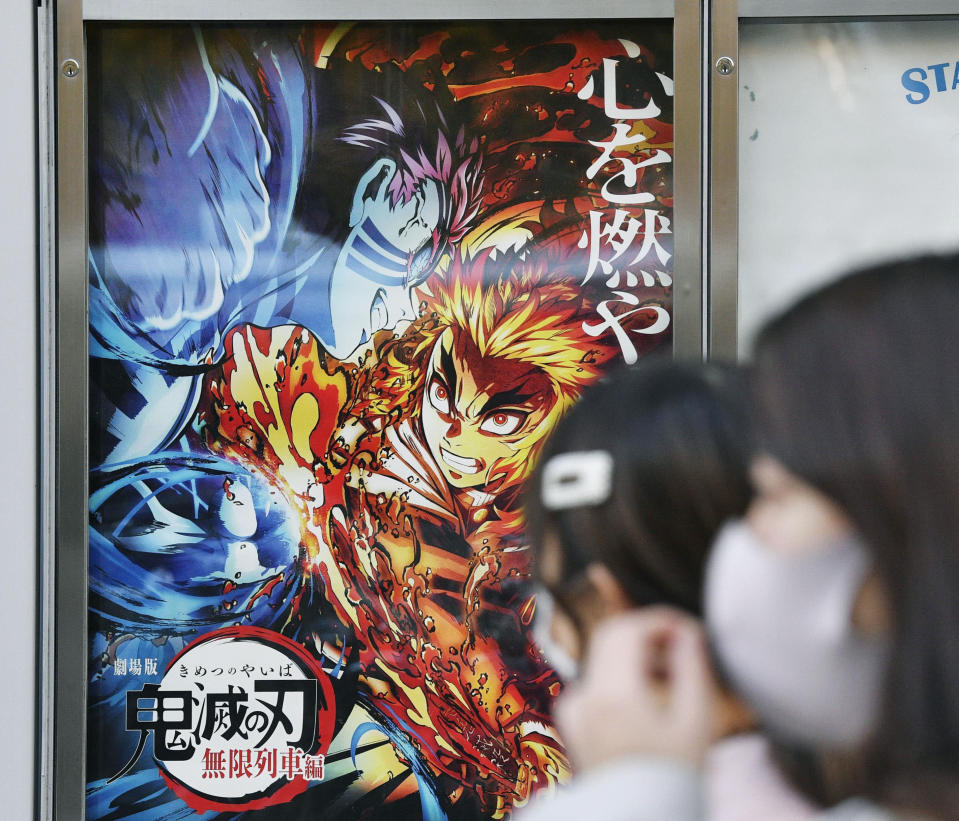 """People wearing face masks walk past a poster of the film """"Demon Slayer: Kimetsu no Yaiba the Movie: Mugen Train"""" at a theater in December 2020. """"Demon Slayer,"""" directed by Haruo Sotozaki, has become the biggest grossing film for Japan, including live-action films, and has struck a chord with pandemic-era Japan, and possibly with the world. (Tsuyoshi Ueda/Kyodo News via AP)"""