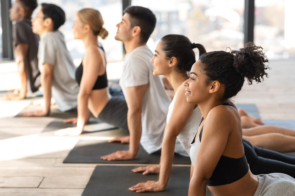 Diverse Multiethnic Men And Women Practicing Cobra Pose During Group Yoga Training Lesson In Modern Studio, Exercising On Mats Together, Meditating While Sitting In A Row, Side View With Free Space