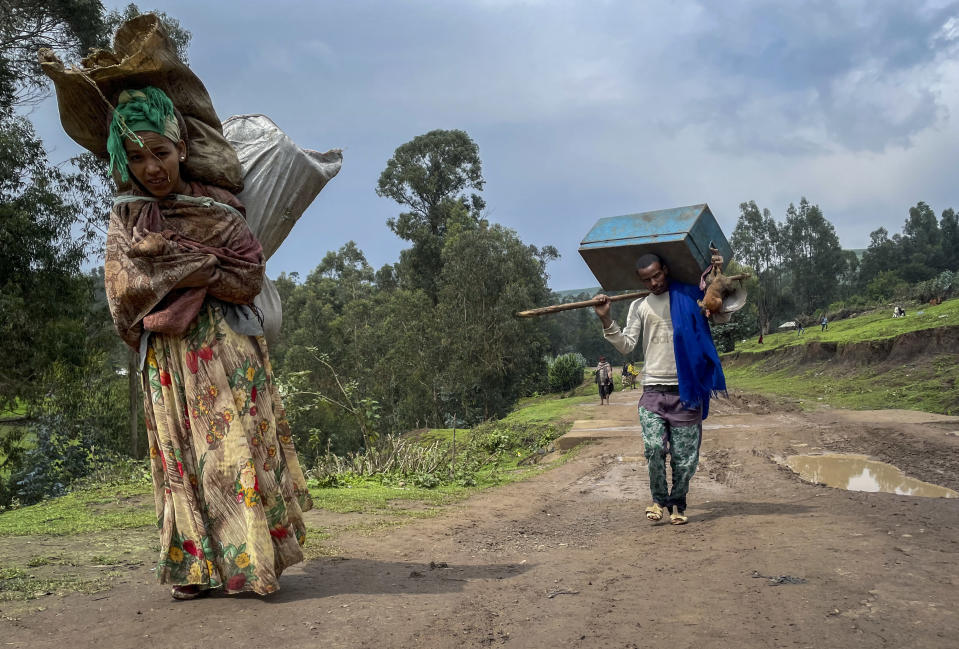 """Senait Ambaw, left, who said her home had been destroyed by artillery, leaves by foot along a path near the village of Chenna Teklehaymanot, in the Amhara region of northern Ethiopia Thursday, Sept. 9, 2021. At the scene of one of the deadliest battles of Ethiopia's 10-month Tigray conflict, witness accounts reflected the blurring line between combatant and civilian after the federal government urged all capable citizens to stop Tigray forces """"once and for all."""" (AP Photo)"""